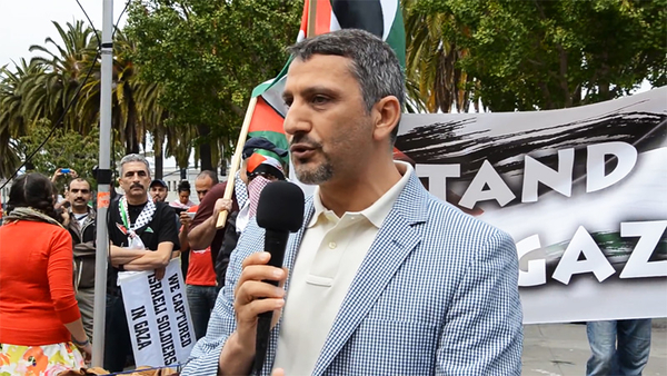 """UC-Berkeley Professor Hatem Bazian demands that Bill Maher be disinvited from speaking at his university. Above, Bazian addresses an anti-Israel rally on July 20, 2014, appearing in front of a man carrying a sign saying """"We captured Israeli soldiers in Gaza"""". (Image source: YouTube video screenshot)"""
